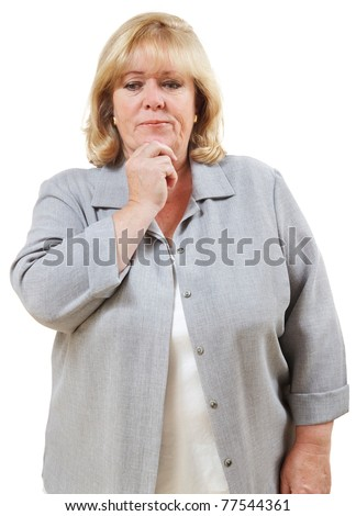 Mature woman looks puzzled, fingers to chin - stock photo