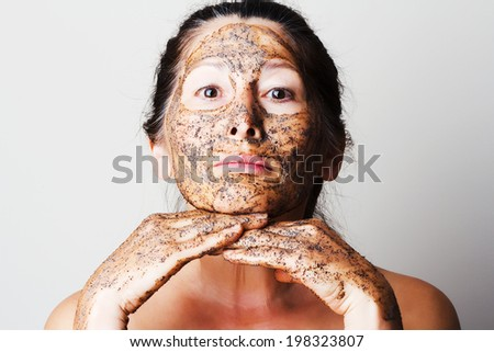 Mature woman making cosmetic mask from coffee, sour cream. - stock photo