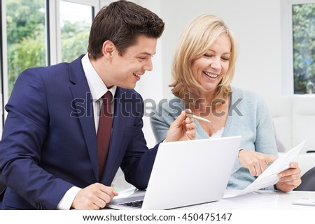 Mature Woman Meeting With Financial Advisor At Home - stock photo