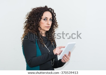 Mature Woman modern use the tablet. She has long curly hair and blacks, with green eyes. - stock photo