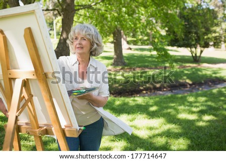 Mature woman painting on canvas in the park - stock photo