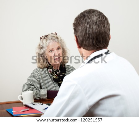 Mature woman patient consults with doctor in his office. Focus is on the woman. - stock photo