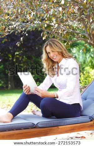 Mature woman portrait. Busy middle age businesswoman sitting at garden at home while working on her laptop. - stock photo