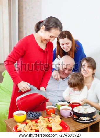 Mature woman pours tea from teapot for her family at home  - stock photo