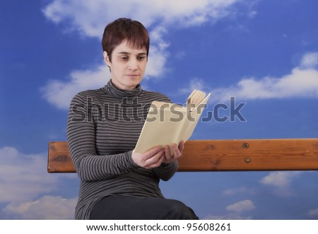 mature woman reading a book, sitting on a bench - stock photo