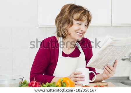 Mature woman reading newspaper and drinking coffee in the kitchen. - stock photo