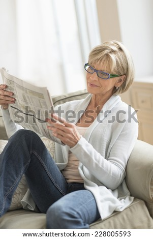 Mature woman reading newspaper while relaxing on sofa at home - stock photo