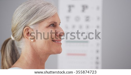 Mature woman receiving eyeglasses from optometrist - stock photo