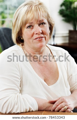 Mature woman relaxing in a comfy chair - stock photo