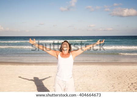 Mature woman relaxing on the beach - stock photo