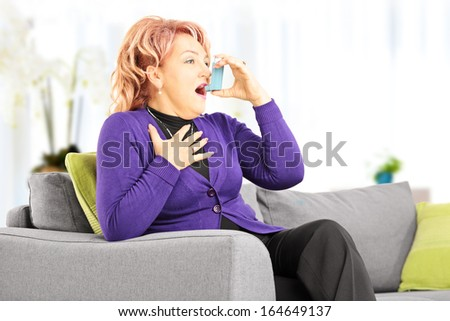 Mature woman seated on a sofa taking asthma treatment with inhaler at home - stock photo