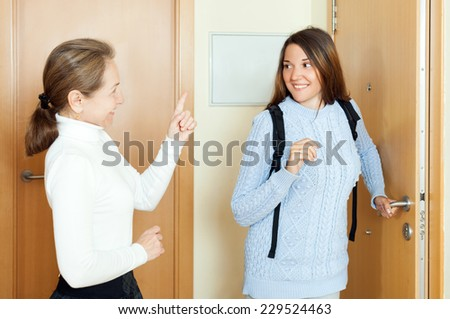 Mature woman sees off adult daughter at the door from home - stock photo