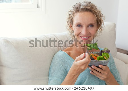 Mature woman sitting and relaxing on a white couch at home while eating a small green salad, home interior. Senior woman eating healthy food. Well being indoors. Lifestyle, smiling. - stock photo