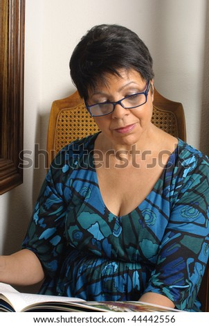 mature woman sitting by window reading a book - stock photo