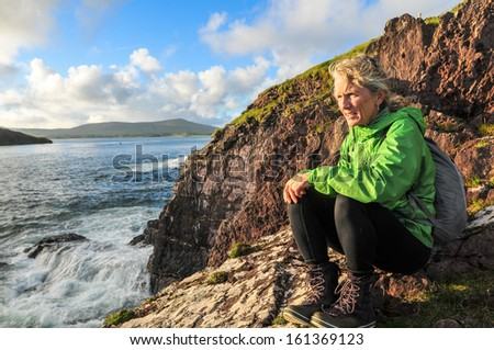 mature woman sitting on cliff above Dingle Bay looking for Fungie, Dingles world famous Dolphin - stock photo