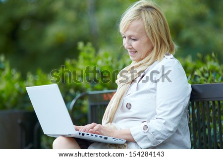 Mature woman sitting on  park bench with  laptop - stock photo