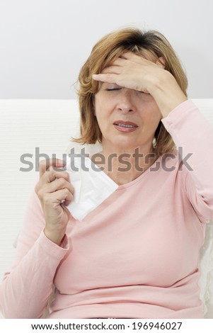 Mature woman sitting on the sofa in the living room and touching  her head in pain. - stock photo