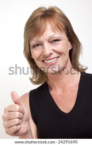 Mature woman smiling and giving a thumbs up signal - stock photo