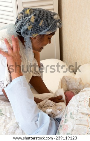 Mature woman smothering her husband in bed after too much snoring - stock photo