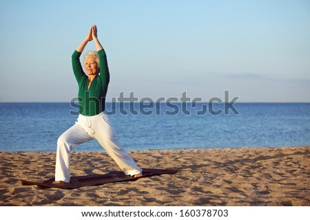 Mature woman stretching on the beach. Senior woman practicing yoga on the beach during morning - stock photo