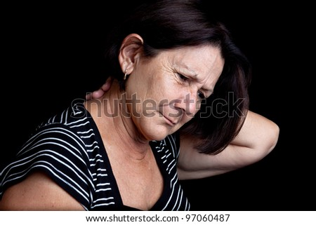 Mature woman suffering from neck or shoulder pain on a black background with space for text - stock photo