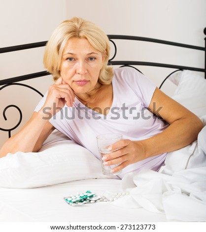 mature woman  taking medicine before falling asleep in bed - stock photo