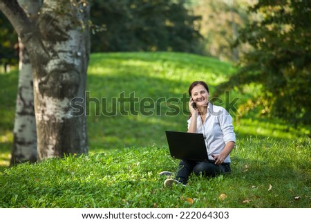 Mature woman talking on smart-phone holding a laptop sitting on the grass in the park - stock photo