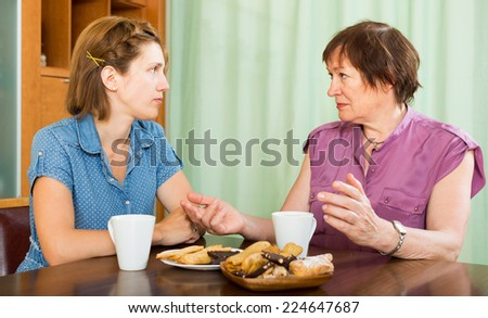 Mature woman talking with her young daughter and drinking coffee - stock photo