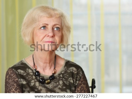 Mature woman thoughtful in her apartment. MANY OTHER PHOTOS FROM THIS SERIES IN MY PORTFOLIO. - stock photo
