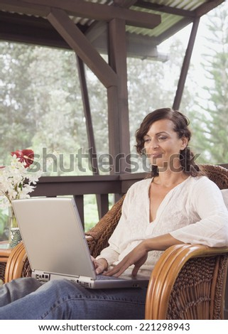 Mature woman typing on laptop - stock photo