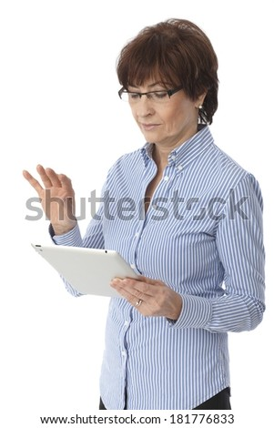 Mature woman using tablet computer, standing over white background. - stock photo
