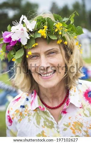 Mature woman wearing flower wreath, Nykoping, Sodermanland, Sweden - stock photo