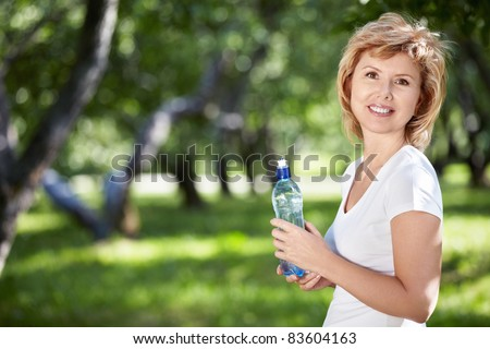 Mature woman with a bottle of water in the park - stock photo