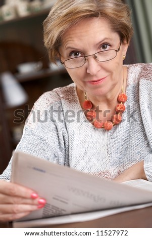 Mature woman with a newspaper - stock photo