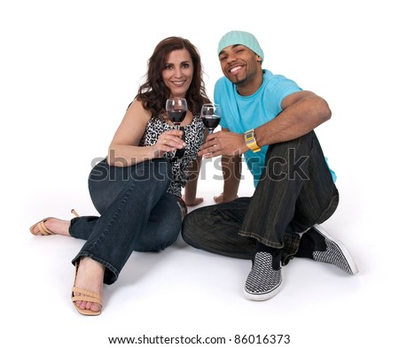 Mature woman with a young man drinking wine, sitting close to each other. - stock photo