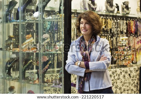 Mature woman with arms crossed standing in front of her store. - stock photo