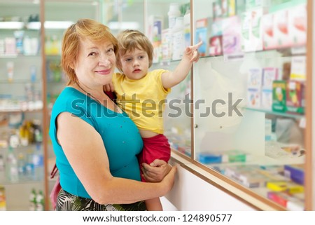 Mature woman with child chooses drugs at the pharmacy - stock photo