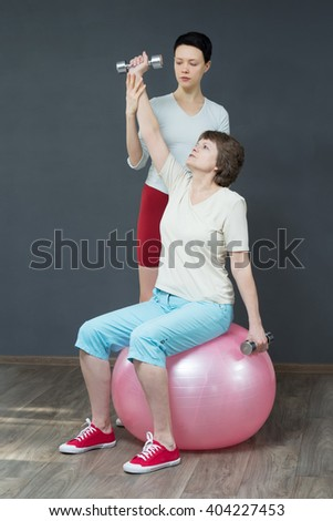 Mature woman with dumbbells and young coach of gymnastics. Woman with fitness dumbbells on the fitness ball. Old woman is smiling in the studio. Mellow woman do her exercises and smile.  - stock photo