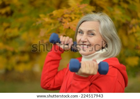 Mature woman with dumbbells in autumn park - stock photo