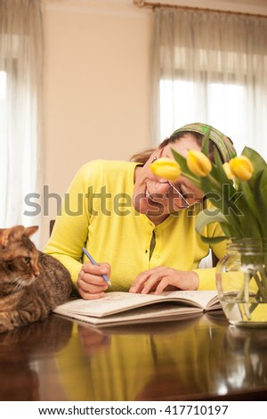 Mature Woman with Eyeglasses and Cat, Domestic life - stock photo