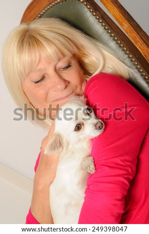 Mature Woman with her dog at home - stock photo