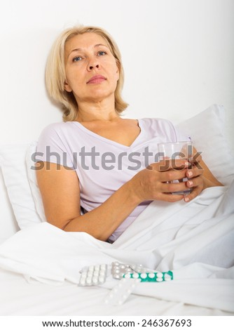 mature woman with pills and vitamins in bed - stock photo