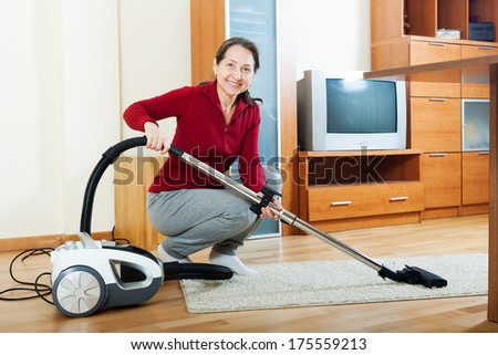 mature woman with vacuum cleaner on parquet floor  - stock photo