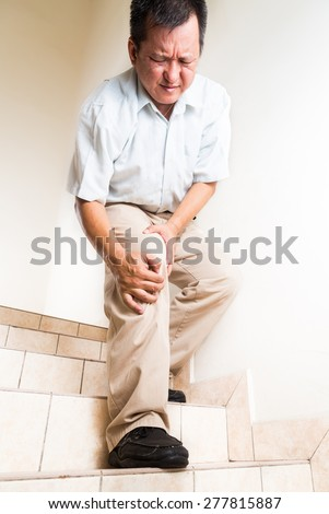 Matured man suffering with knee joint pain descending stairs - stock photo
