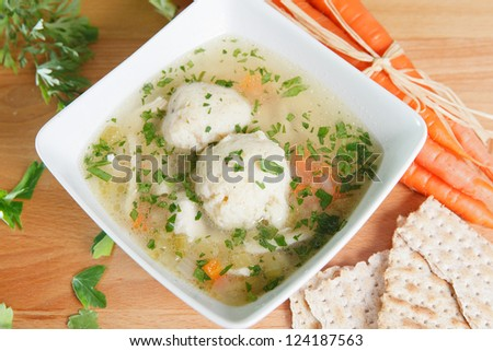 Matzah Ball Soup garnished with carrots and Matzo crackers - stock photo