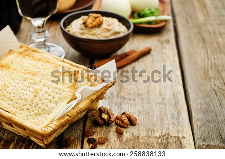 Matzah, wine, eggs, chicken, greens and haroset on a dark wood background, traditional food for the Pesach. tinting. selective focus - stock photo