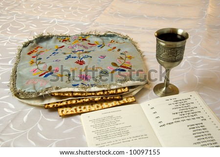 matzo in an antique embroidered matzo cover with kiddush cup of wine and traditional passover haggadah text - stock photo