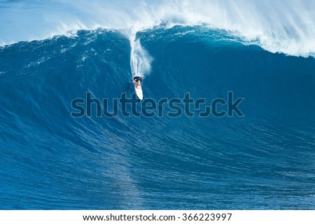 """MAUI, HI - JANUARY 16 2016: Professional surfer rides a giant wave at the legendary big wave surf break known as """"Jaws"""" on one the largest swells of the year. - stock photo"""