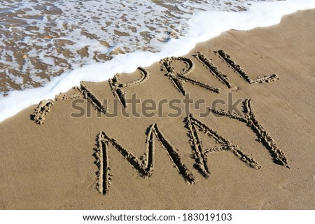 May is coming concept - inscription April and May written on a sandy beach, the wave is starting to cover the word April.  - stock photo