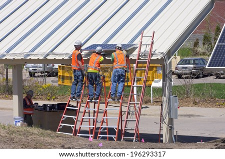 MAY 22, 2014: Workers at Great River Energy install solar carport in Maple Grove, Minnesota. The building earned an award given to facilities that demonstrate energy efficiency and sustainability. - stock photo